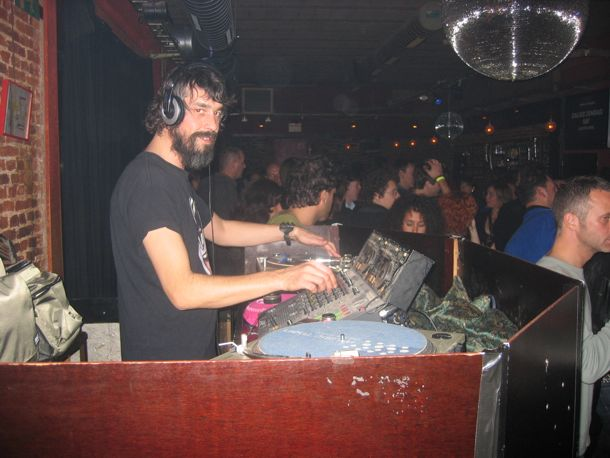 photo of DJ smiling at the camera in a dance club