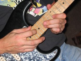 closeup photo of Andy tapping on his Strat